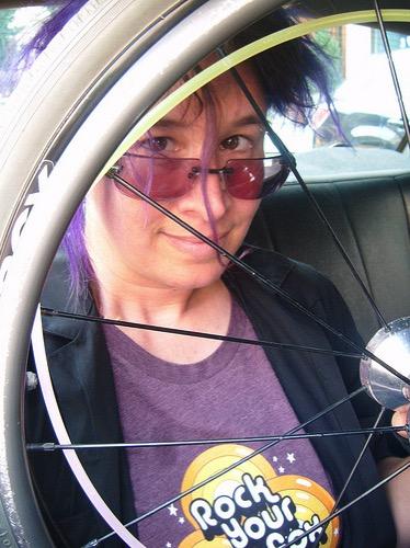 liz with a wheelchair wheel in a taxi