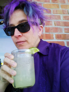 liz in sunglasses with a drink in hand