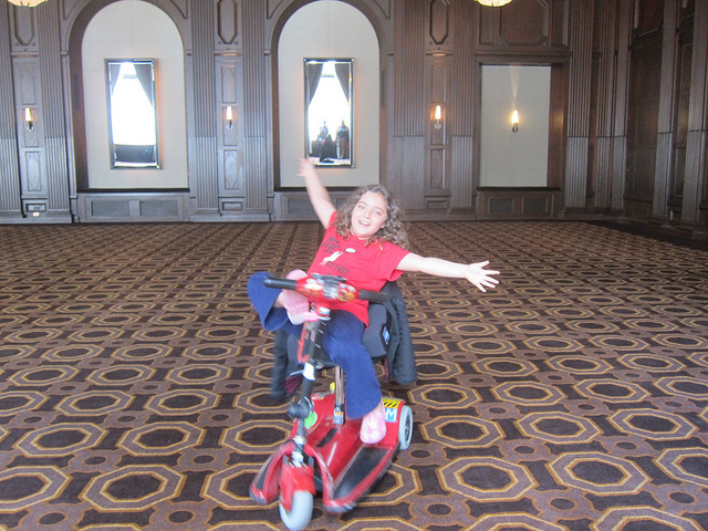 kid on scooter in ballroom