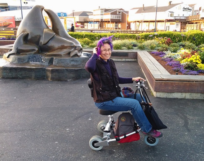 Liz on travelscoot with sealions statue